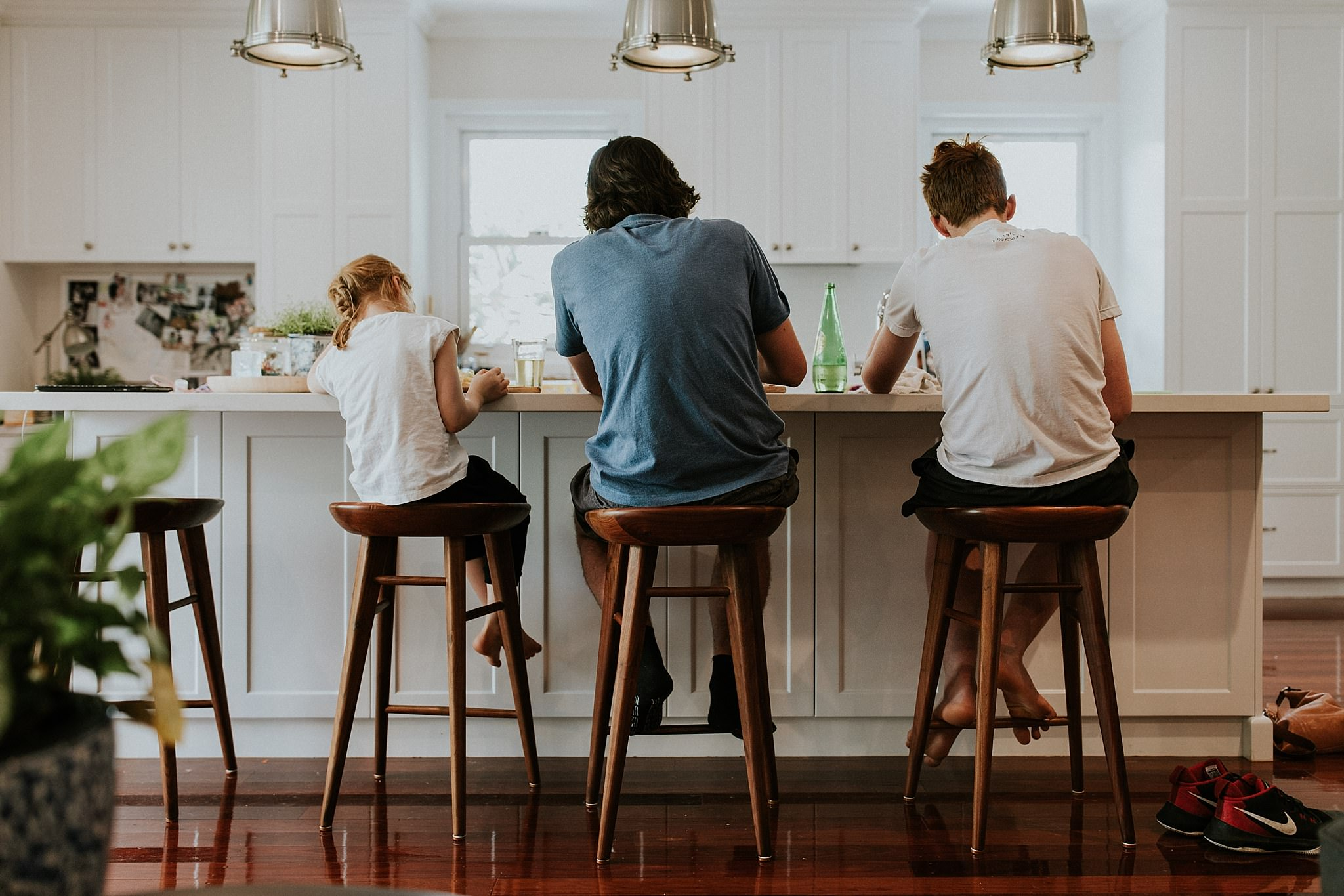 Family photo shoot with father and children sitting at kitchen bench