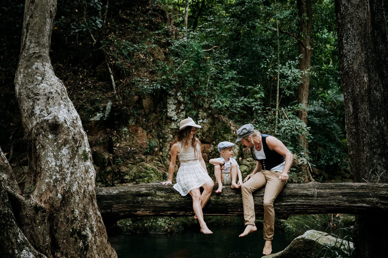 Family sitting on a fallen tree in the incredible Jourama Falls National Park