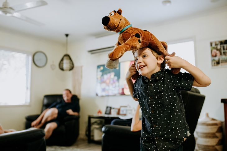 Young boy in lounge room with Scooby doo dog on his head as a hat