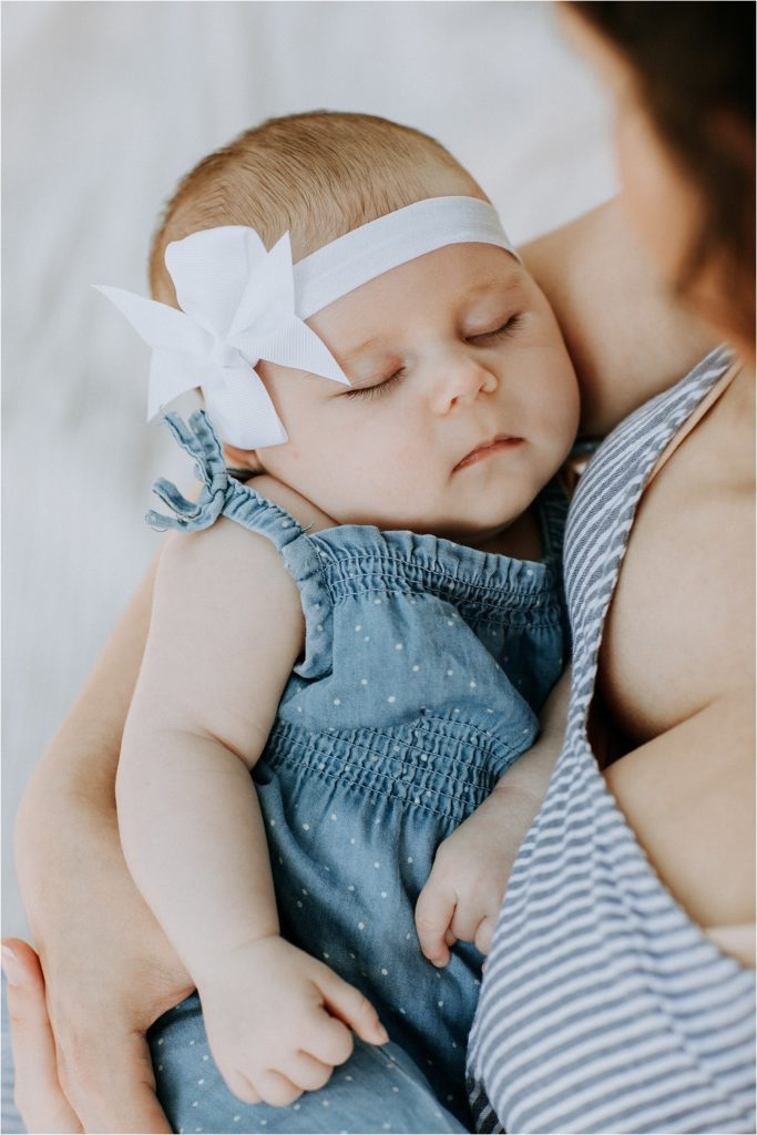 Newborn Baby girl fast asleep in her mothers arms.