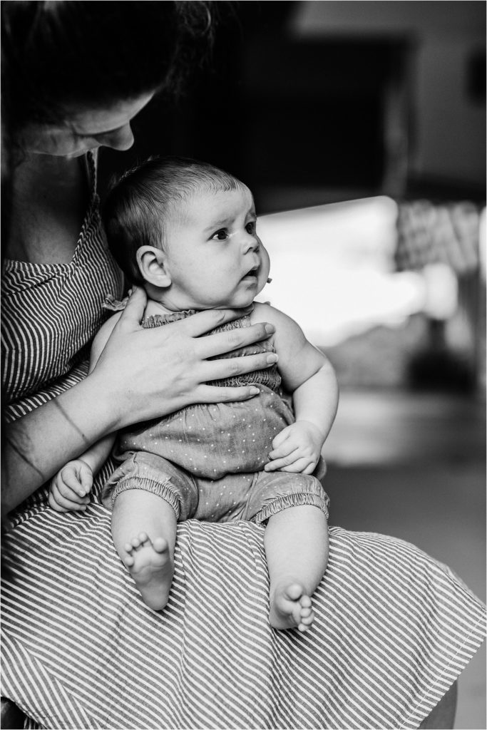 black and white photo of baby girl looking towards her dad