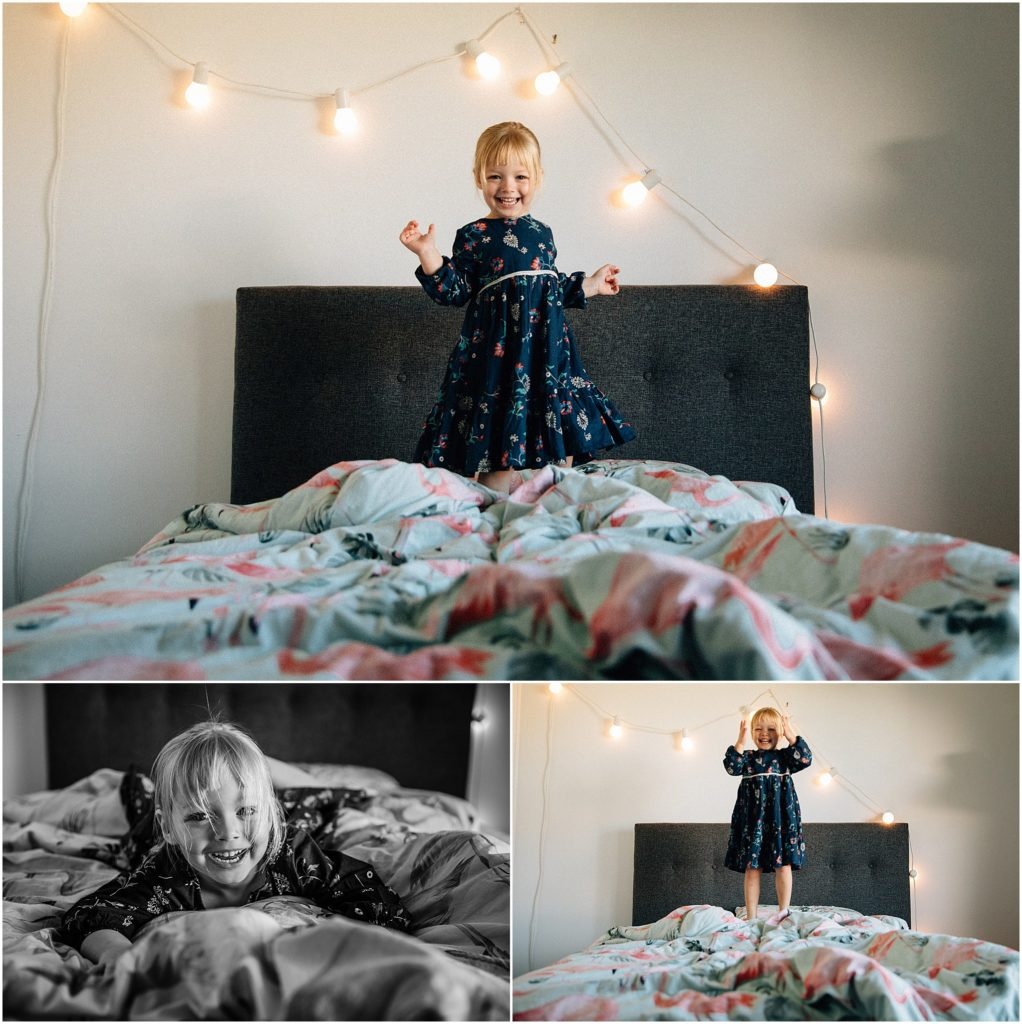 Young girl playing on bed with fairy lights