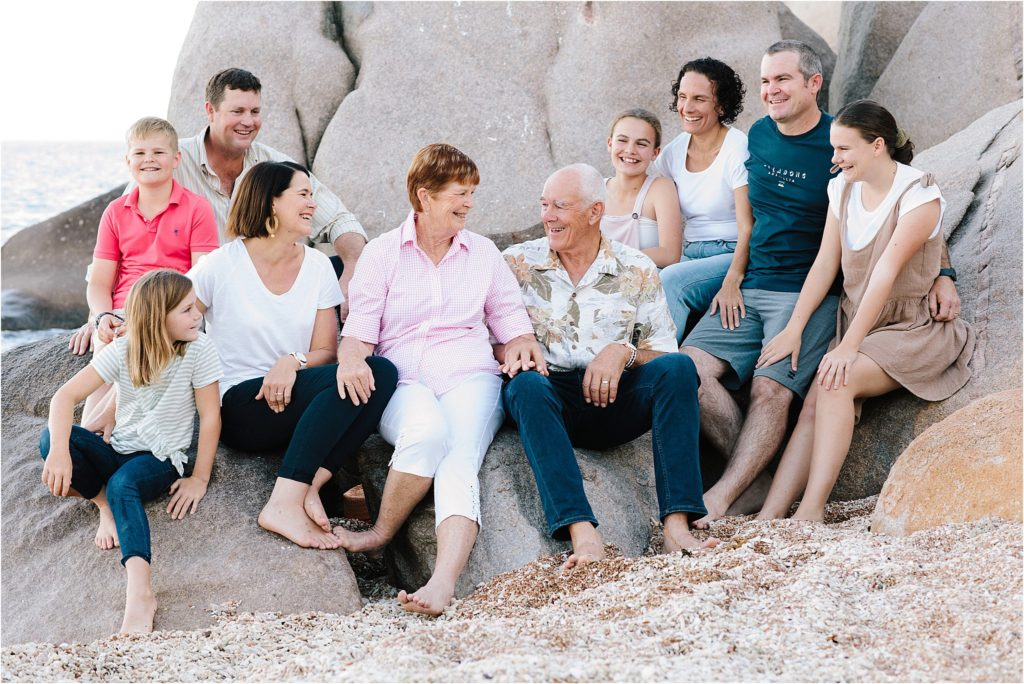 Family and grandparents on beach at Magnetic Island sitting on rocks.