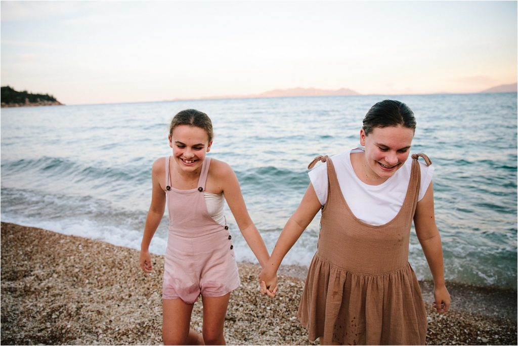 Sisters holding hands walking on Magnetic Island beach with ocean in background.