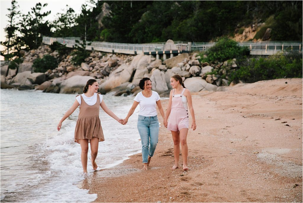 Mother and two older daughters holding hands walking down beach.