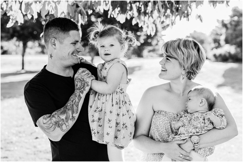 Black and white family photo of husband and wife with two little girls.