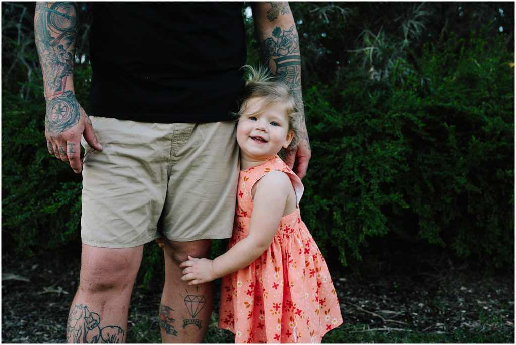 Young girl holding onto father's leg.