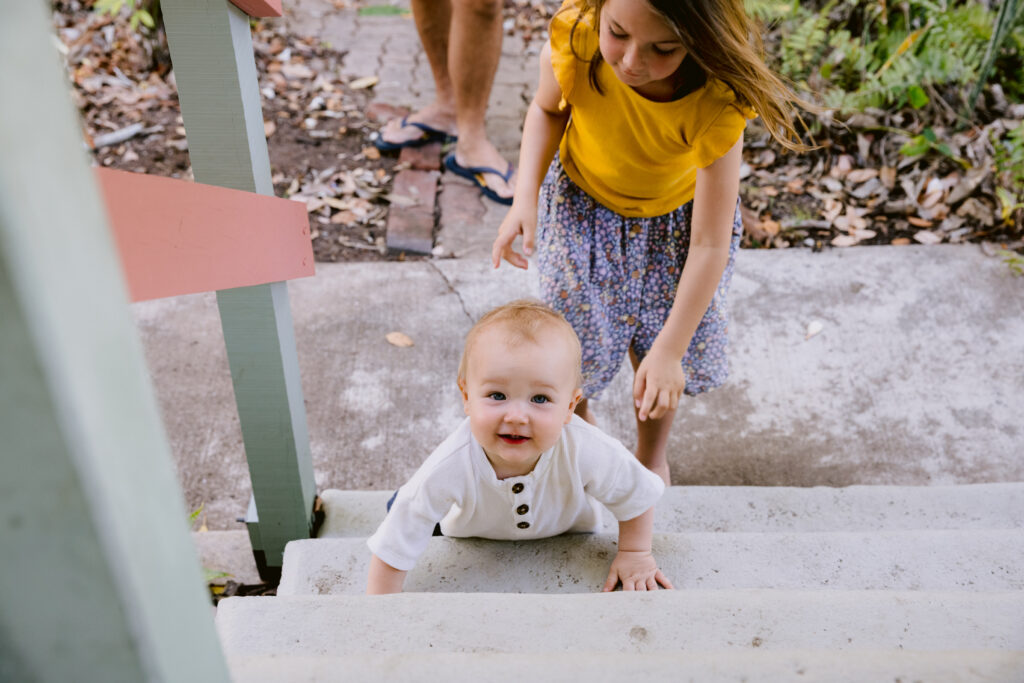 The baby is crawling the stairs and the big sister is ready to help.