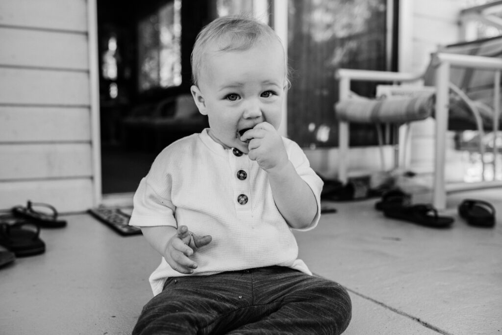 The baby is sitting on the floor eating an Anzac biscuit.