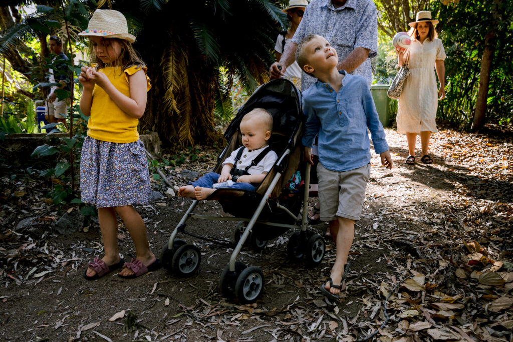Grandfather is pushing the pram with grandchildren on either side of the pram walking down the track to Geoffrey Bay. The young boy looks up to explore what is in the trees.