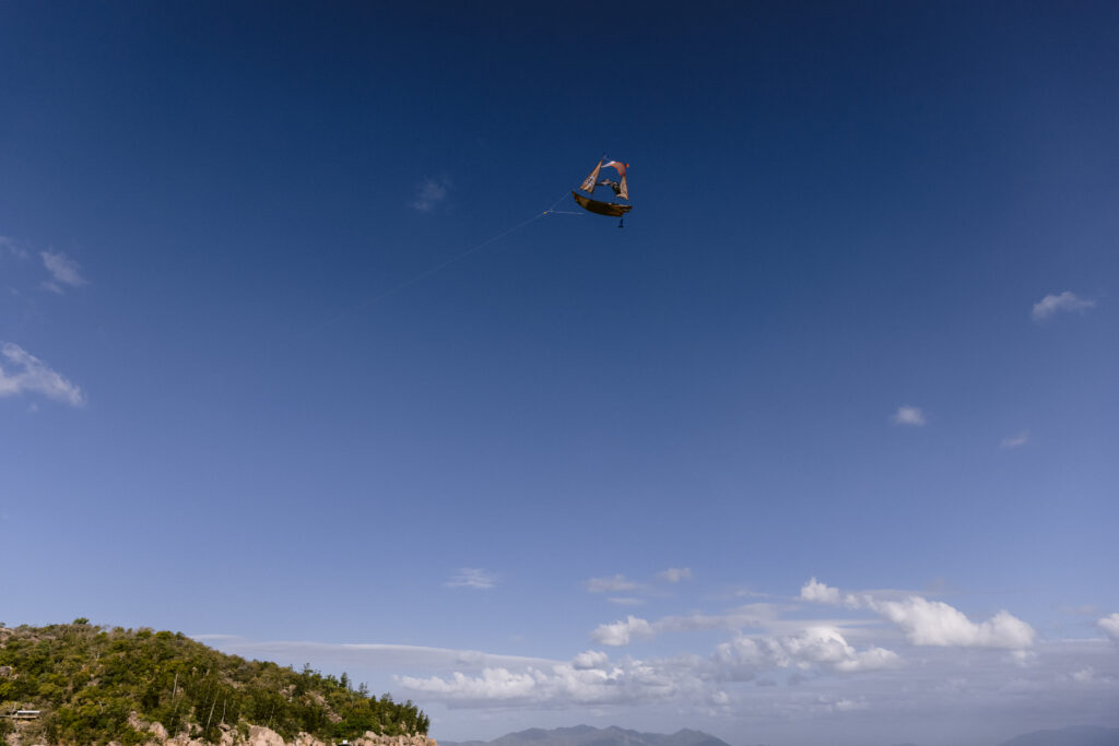 The pirate ship kite flies high in the blue sky on Geoffrey Bay at Magnetic island.
