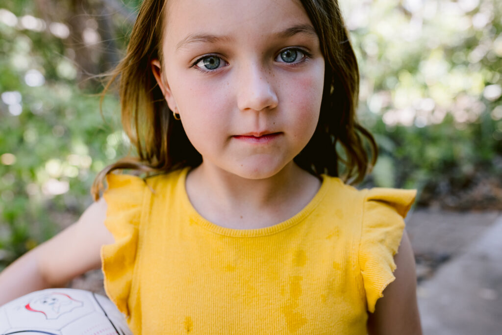 Photo of a young girl looking directly at the camera with a basketball tucked under her arm.