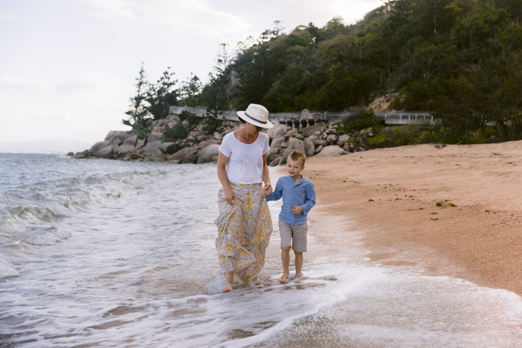 Mother and son walk along the beach as the waves wet the feet.