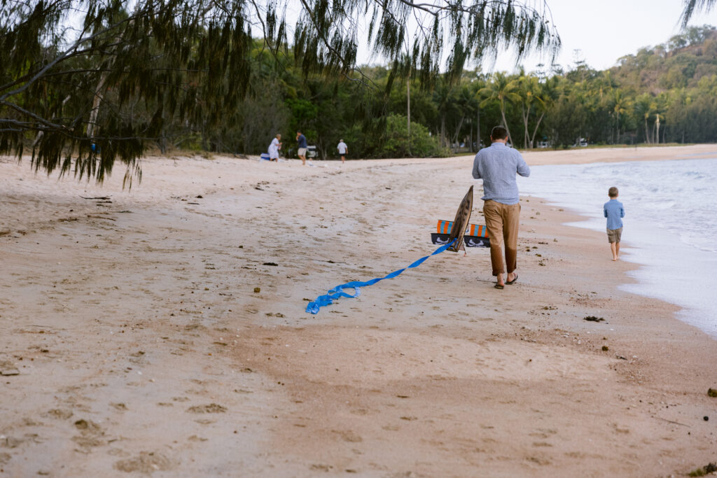 The Uncle winds up the kite string as he walks along the beach.