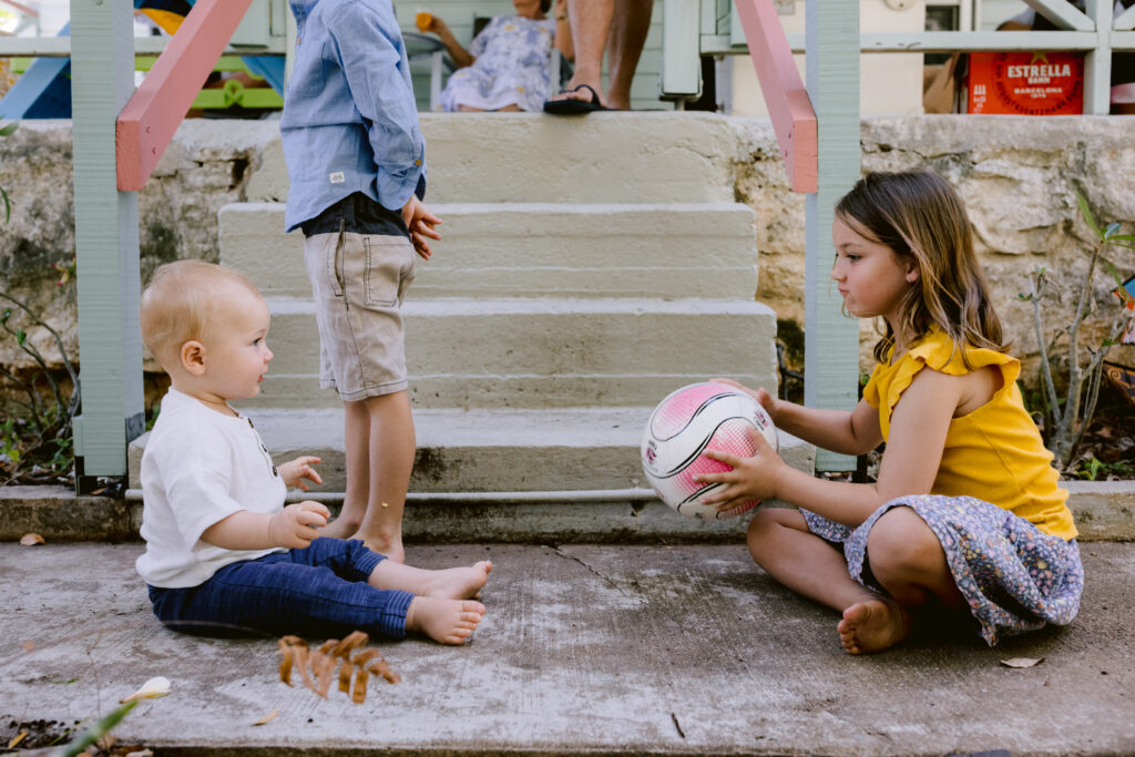 Big sister is playing ball games with the baby on the concrete path in front of the beach house.