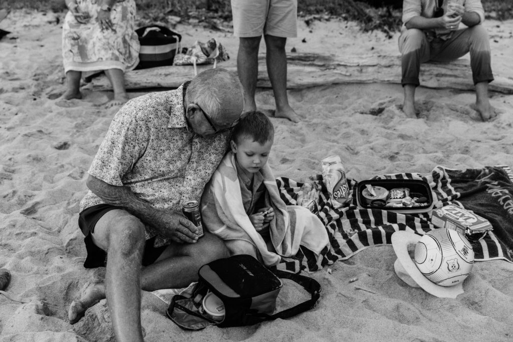 Grandfather sits next to his grandson on the beach towel and chats to him.