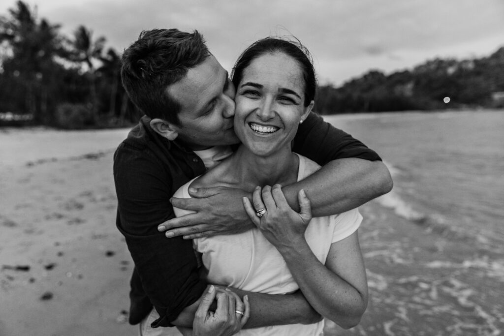 Husband embraces his wife lovingly on the beach as the sun sets at Magnetic Island