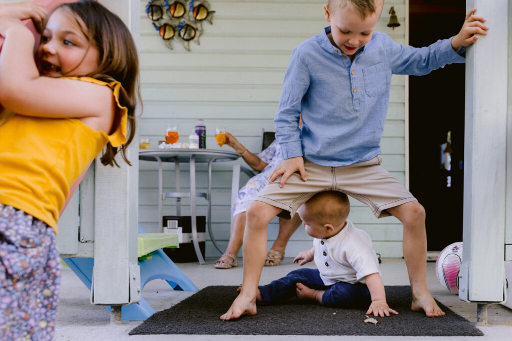 The big sister is swinging on the hadn't rails. The baby brother is crawling under the big brothers legs.