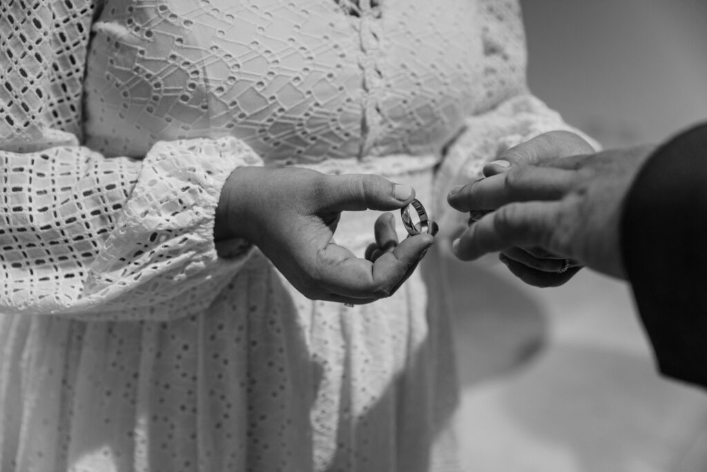 Hannah places the wedding ring on Terry's finger during their elopement ceremony.