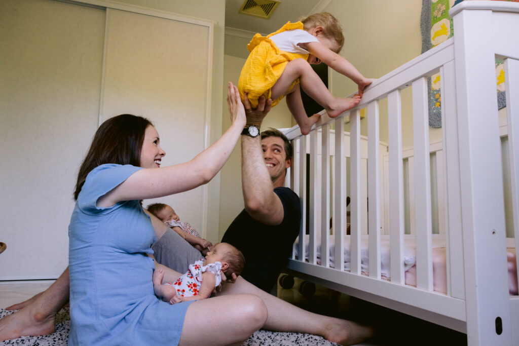 Mum and Dad each have a twin baby in their lap and with one hand each the help the toddler climb over the cot rail.