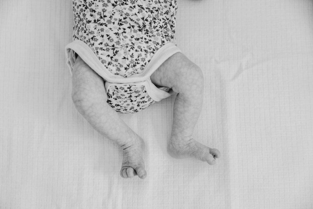 The little legs and toes of the other twin baby girl.