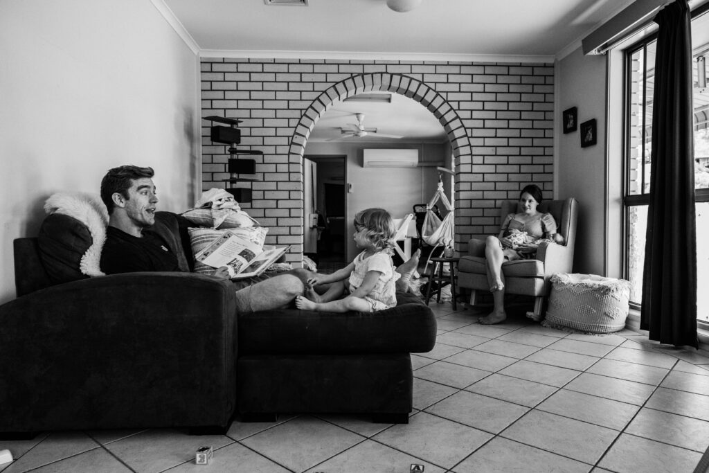 Dad reads a book on the couch to the toddler while Mum sits in the rocking chair with the twin girls.