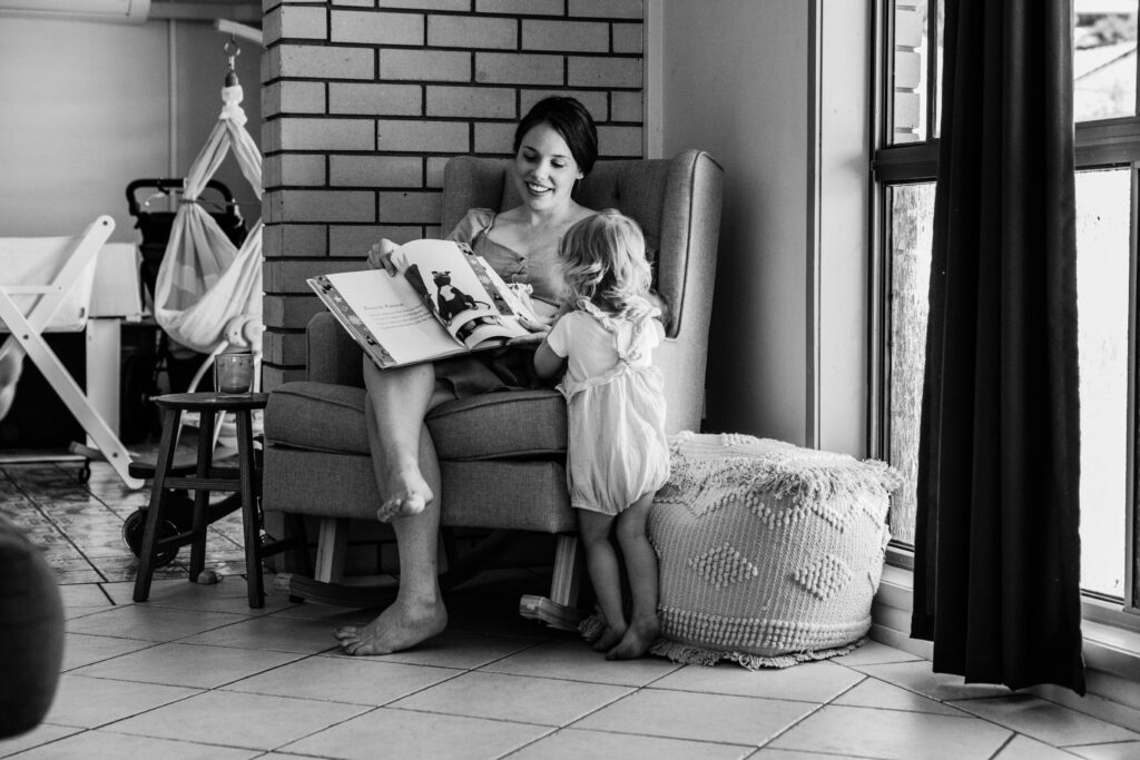 Mum is sitting in the rocking chair. The twins are on her lap and covered with a book that she is reading to the toddler.