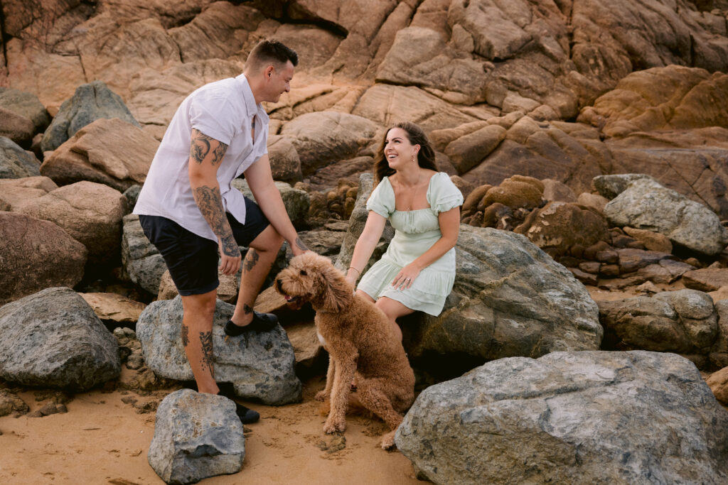 The engaged couple Trudy and Beau are smiling looking at each other. Their dog mopey is sitting at the feet on the beach.
