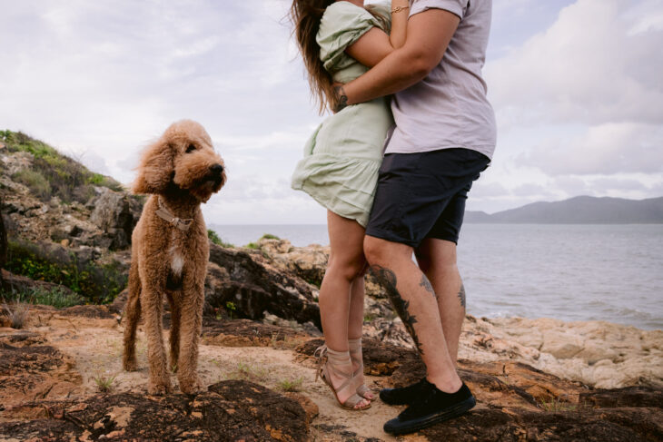 Trudy and Beau's engagement photo. Trudy is on tiptoes kissing Beau and Mopsy the groodle is standing beside.