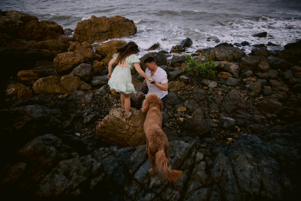Beau takes Trudy's hands and helps her adventure across the rocks. Mopsy the Groodle follows.