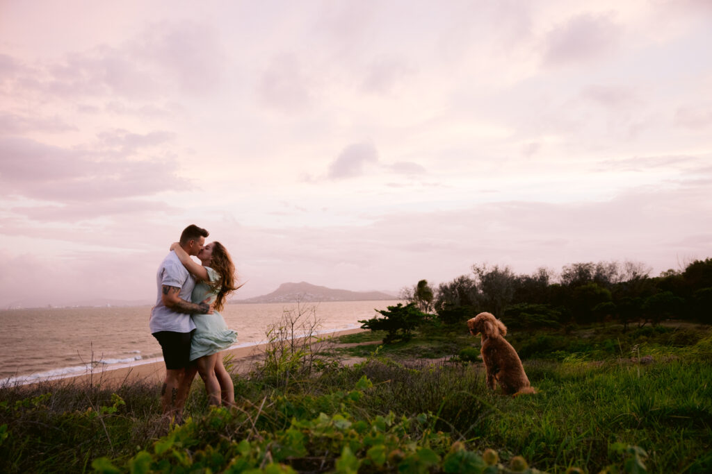 Engagement photo of Trudy and Beau with their dog at sunset on a hill near the beach.