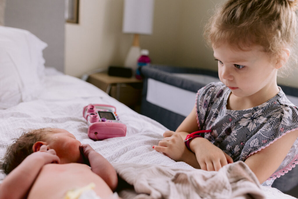 Big sister who is still very young stares at her brand new born baby brother examining him.