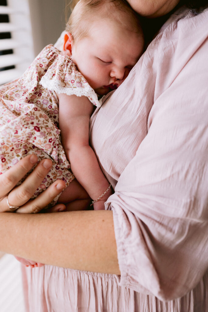Newborn baby girl is being held by her Mother. With her beautiful squishy cheeks.