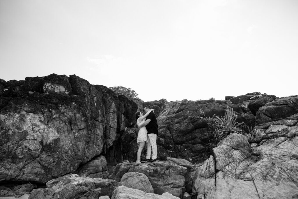 Billy and Jess stand together on a large rock talking together.