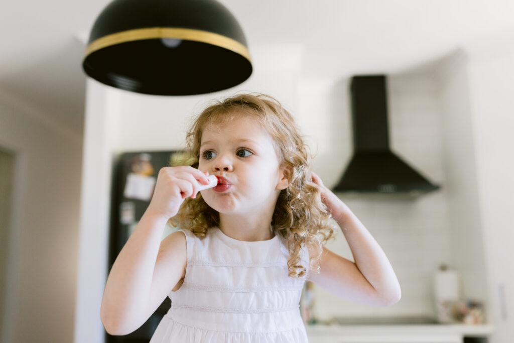 Pip is sitting on the kitchen bench with her lips pouted while applying her lipgloss. She holds back her hair with the other hand.