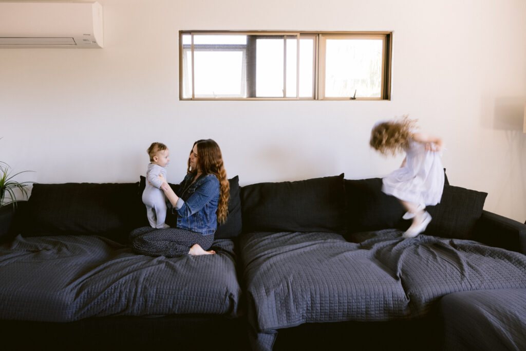 Mum holds baby while little girl jumps on the couch