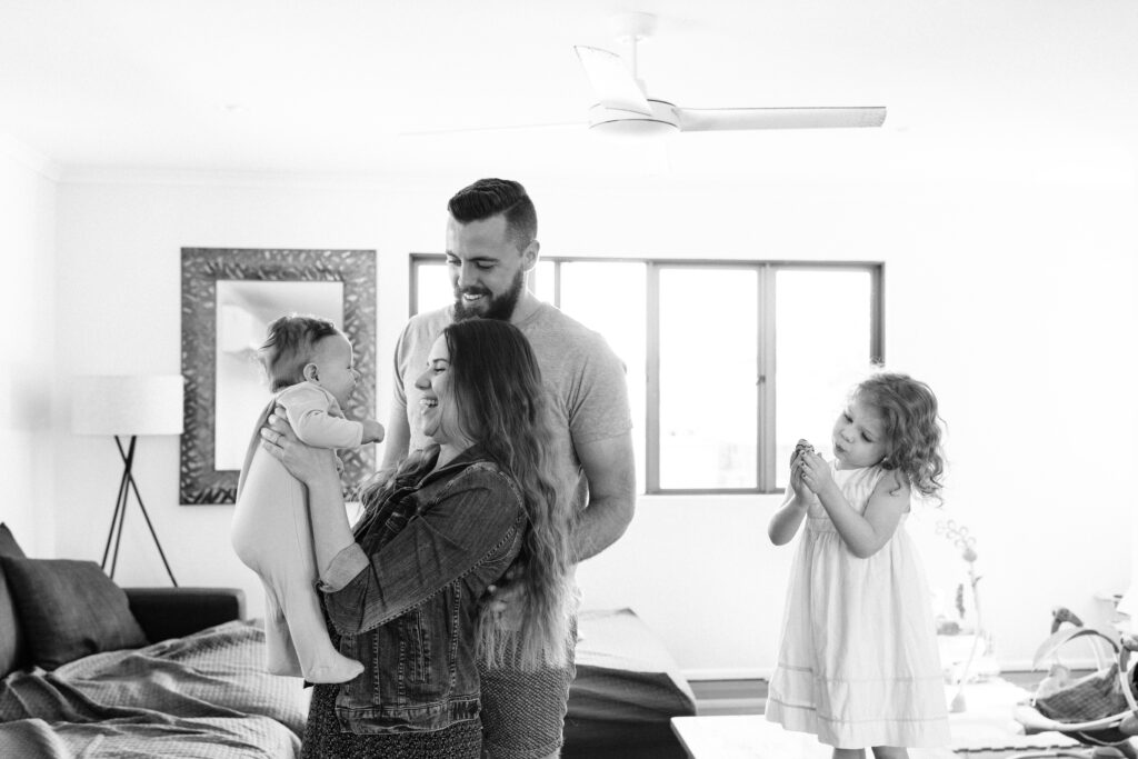 The mum is hold up the baby, the dad is standing beside the mum smiling at the baby. The little girl stands separately on the coffee table looking at a toy she has picked up.