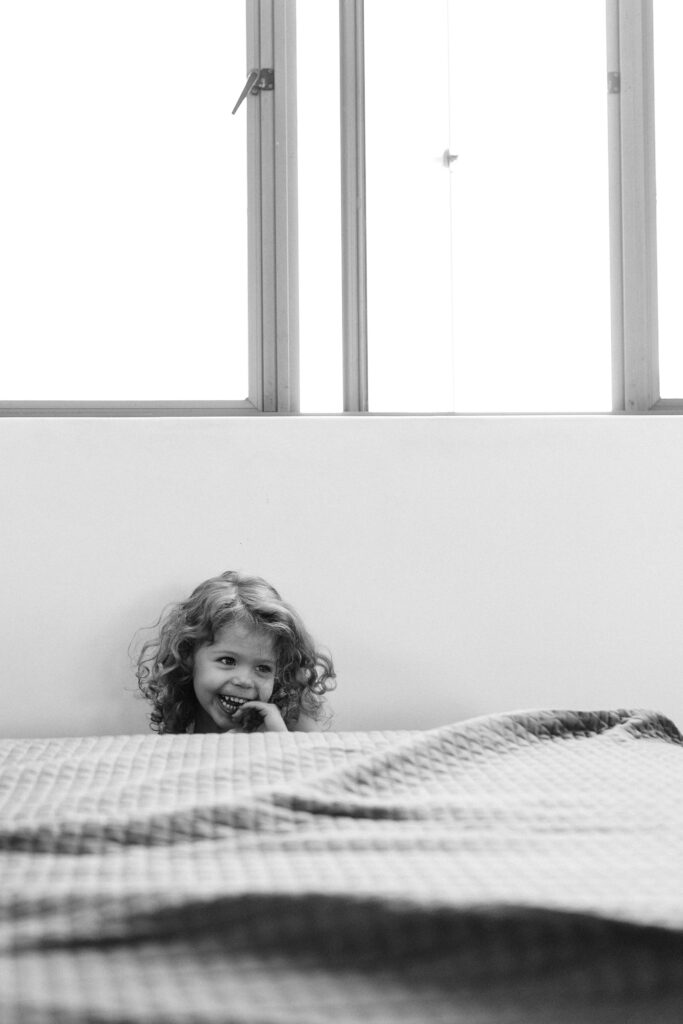 Little girl in hiding behind the couch and pops up and smiles