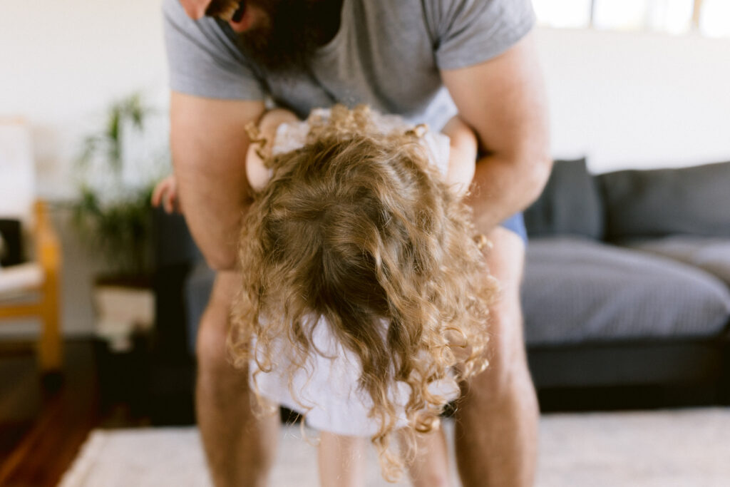 Dad playfully dances with his little girl