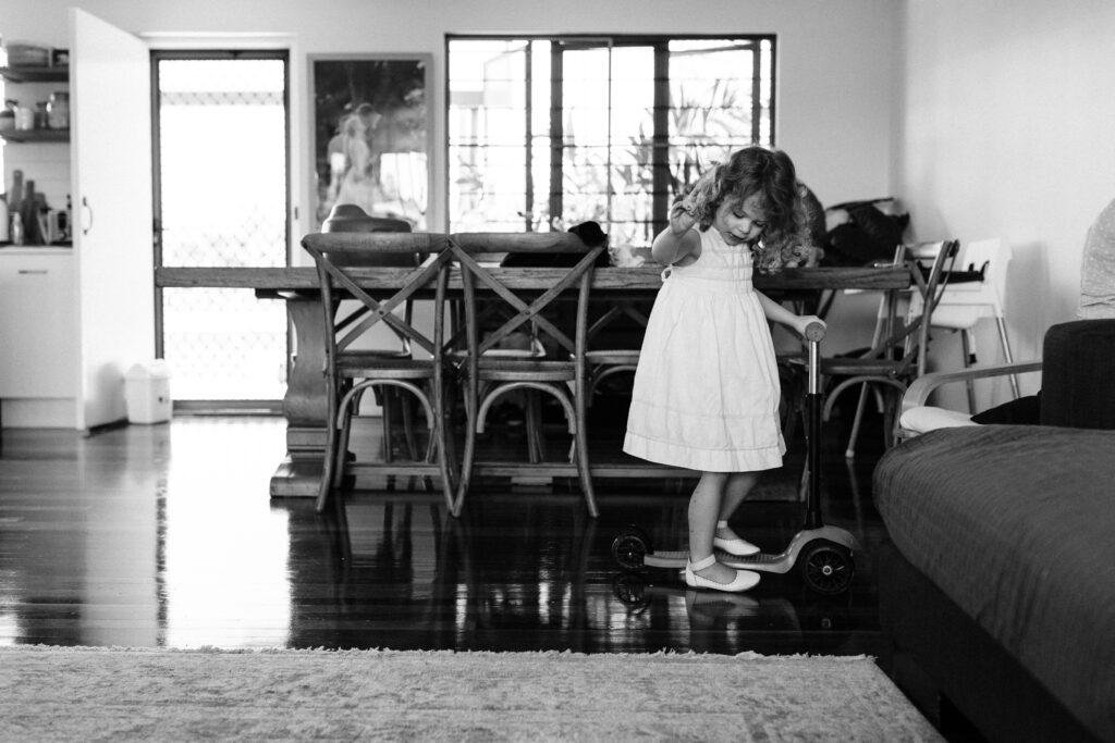 Pip stands on her scooter near the dining room table. She is wearing a white dress and white shoes.