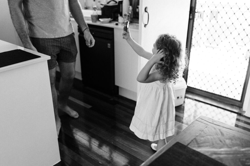Pip shows her Daddy a rock that she has painted in the kitchen.