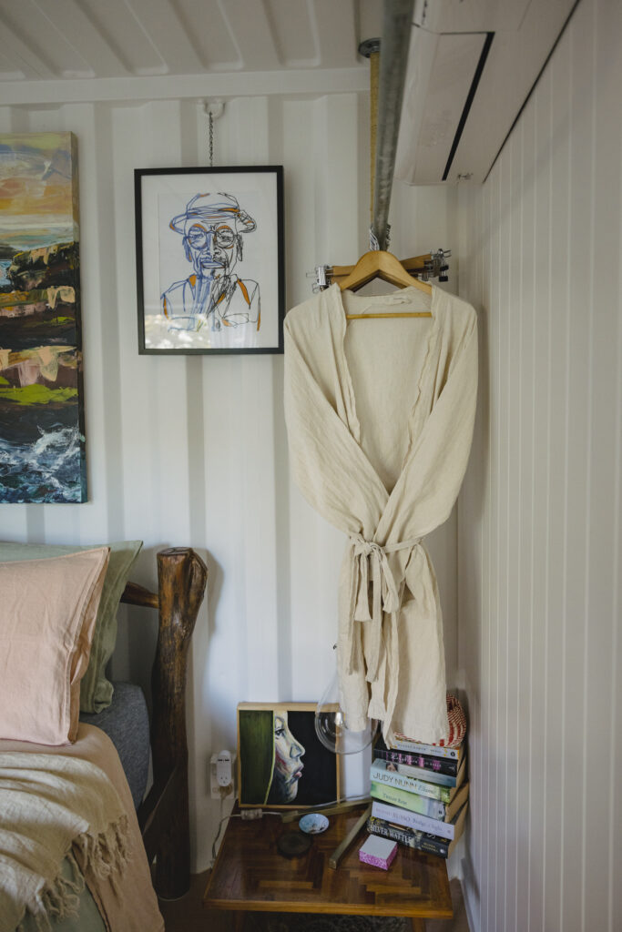 Beside the bed hangs The Bed Threads Linen Robes. Stacks of books sit on the table beside the bed.