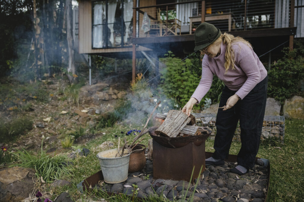 Elyse starts the fire with precut wood and kindle stored in metal buckets.