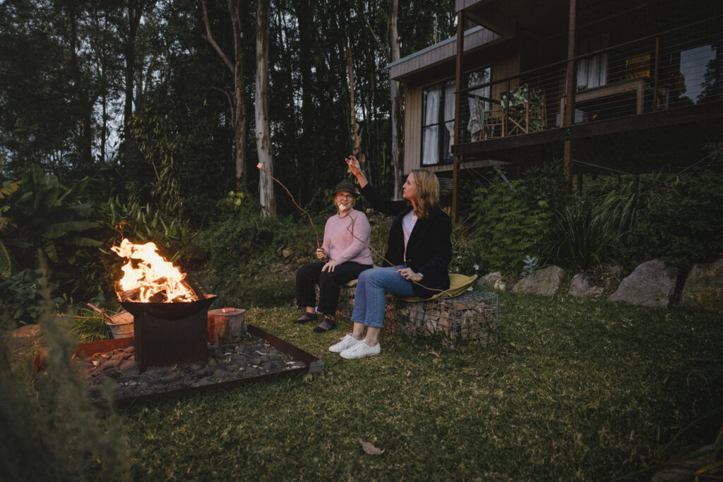 Katie and Elyse sit by the fire out the front of the Airbnb The Wilds Container Home roasting marshmallows.