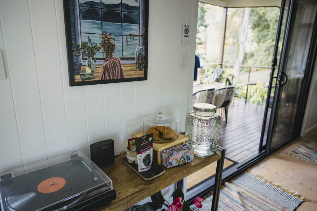 On a side table sits a record player. Fresh croissants, napkins and a water dispenser.