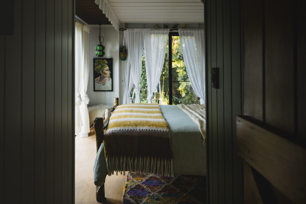 Looking at the bedroom from the hallway. Art hangs on the wall with a glass pendant light near it.